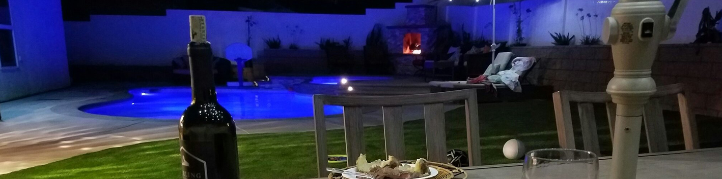 backyard table with bottle of wine and pool in background